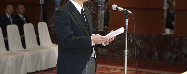 社葬会場で祭壇に向かい奉書の弔辞を奉読する弔辞者