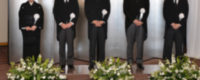 社葬の立礼に喪章をつけてモーニングや喪服で並ぶ葬儀委員長や喪主や遺族