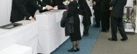 お葬式に参列するために喪服を着て受付をする人々