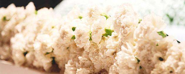 祭壇前の献花台に手向けられたカーネーションの献花