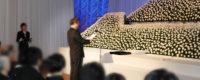 社葬の厳かな祭壇の前で故人への思いのこもった弔辞を読む社員代表弔辞者