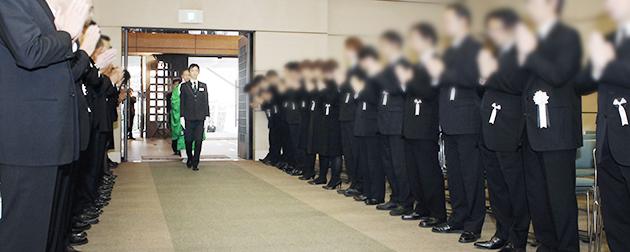 合同葬式場への導師入場のお迎えにあたり合掌をして整列する合同葬主催企業の社員