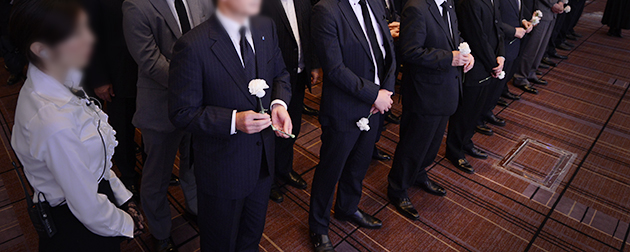 ホテルのお別れの会で献花の列に並ぶダークスーツの参列者