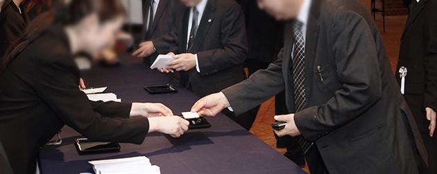 社葬の参列者を名刺で受付けし案内する受付スタッフ