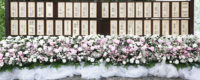 社葬式場の外に並べて飾られた芳名板と多くの供花