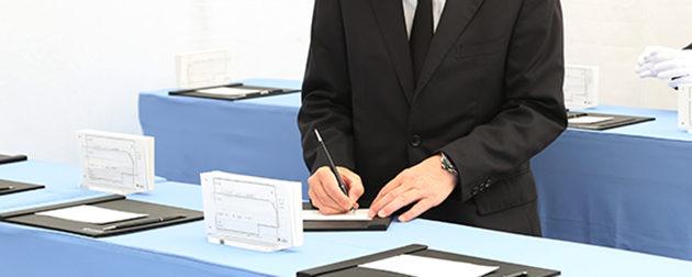 社葬参列のために記帳台で受付用の記帳をする参列者