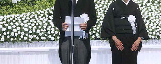 モーニングを着用する葬儀委員長と和装の喪服を着用する喪主
